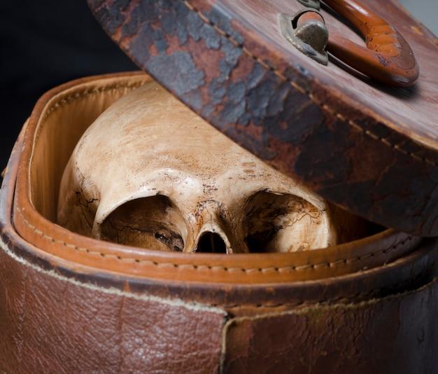 Stillleben mit dem menschlichen schädel werden in den alten ledernen kasten gelegt, der auf schwarzem hintergrund getrennt wird