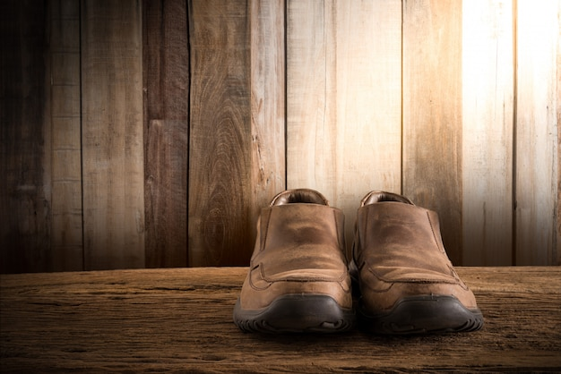 Stillleben mit den schuhen der männer auf hölzerner tischplatte gegen schmutzwand