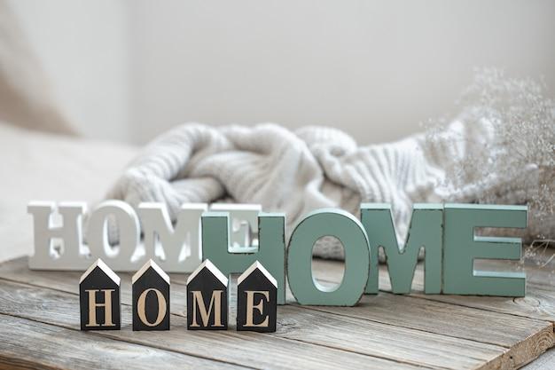 Stillleben mit den worten zuhause für wohnkultur auf unscharfem hintergrund. das konzept von gemütlichkeit und komfort zu hause.