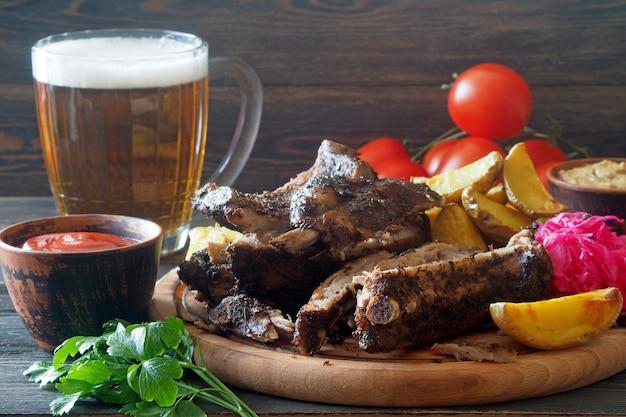Stillleben mit einem becher bier und snacks - geräucherte rippen und gebackene kartoffelschnitze