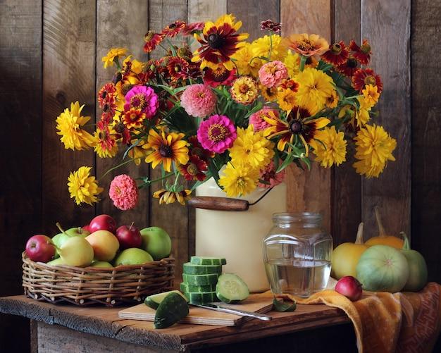 Stillleben mit einem blumenstrauß aus gartenblumen, kürbissen, gurken, birnen und äpfeln.