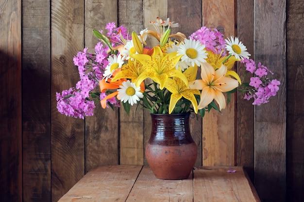 Stillleben mit einem blumenstrauß aus lilien, gänseblümchen und phlox in einem tonkrug