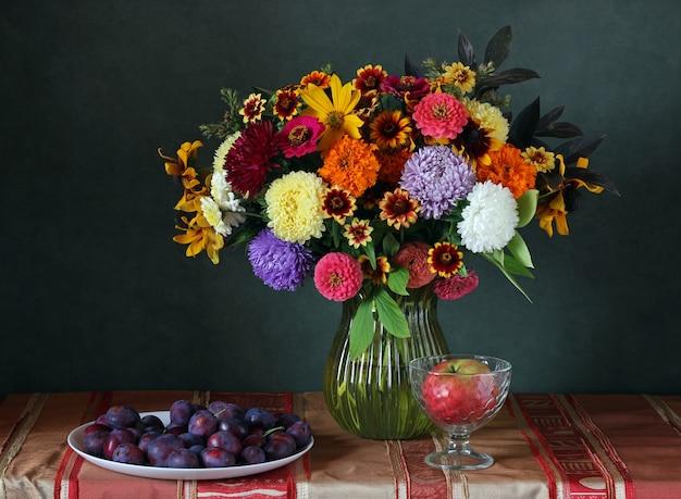 Stillleben mit einem bouquet von herbstblumen, äpfeln und pflaumen.