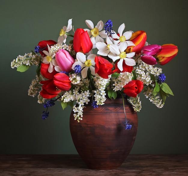 Stillleben mit einem frühlingsstrauß aus narzissen, tulpen und kirschzweigen in einem tonkrug