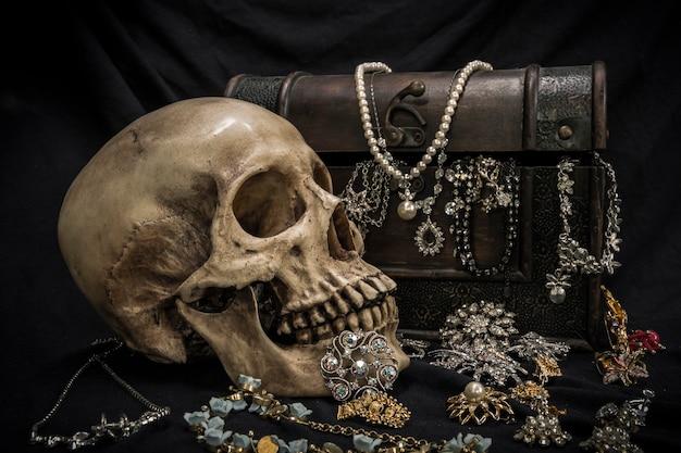 Stillleben mit einem menschlichen schädel mit alter schatztruhe und gold, diamant