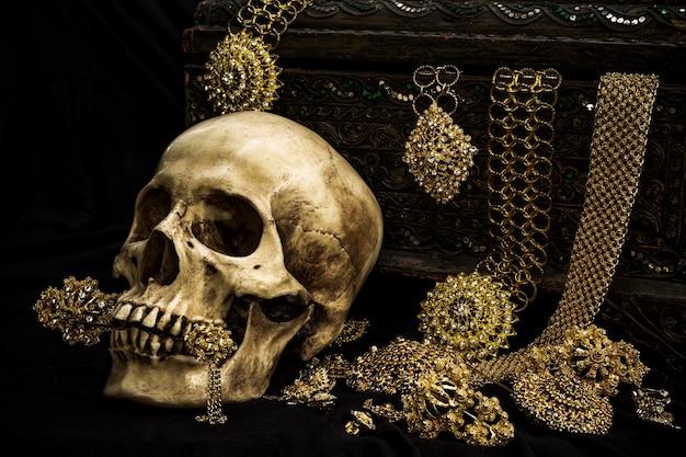 Stillleben mit einem menschlichen schädel mit alter schatztruhe und gold