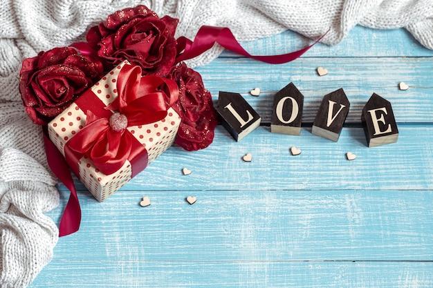 Stillleben mit einem schön verpackten geschenk, blumen und dekorativen elementen auf einer holzoberfläche. valentinstag urlaubskonzept.