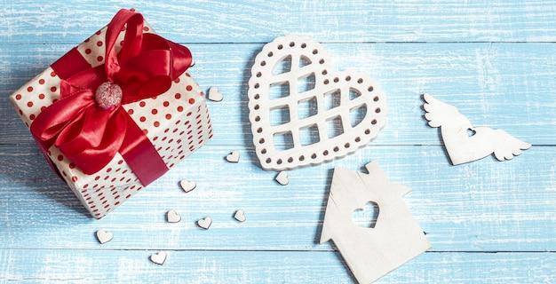 Stillleben mit einem schön verpackten geschenk und dekorativen elementen auf einer holzoberfläche. valentinstag urlaubskonzept.