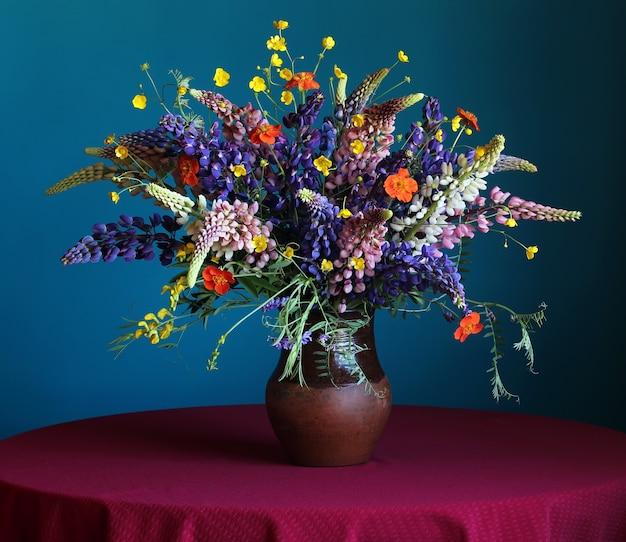Stillleben mit einem sommerblumenstrauß von lupine und von butterblumeen im krug auf dem rundtisch mit einer roten tischdecke auf einem blauen hintergrund.