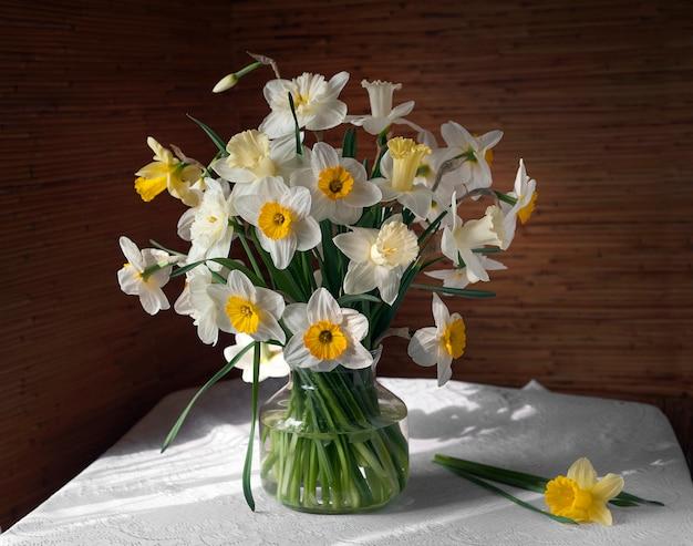 Stillleben mit einem strauß narzissen in glasvase auf einem tisch mit weißer tischdecke