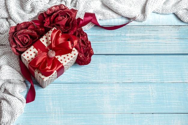 Stillleben mit einem wunderschön verpackten geschenk, blumen und einem gestrickten element auf einer holzoberfläche. valentinstag urlaubskonzept.
