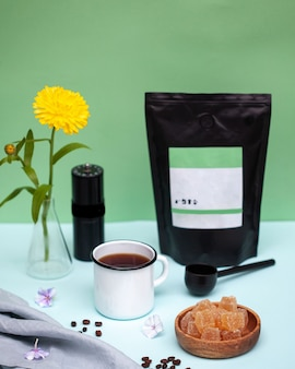 Stillleben mit einer kaffeetasse, einem paket kaffeebohnen und einer gelben blume
