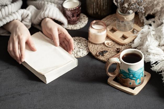 Stillleben mit einer schönen tasse und weiblichen händen. eine intime, heimelige atmosphäre. dekorative gegenstände.