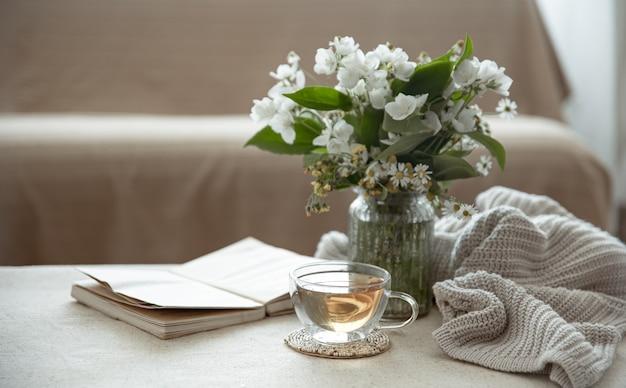 Stillleben mit einer tasse kräutertee, einem strauß wildblumen, einem buch und einem strickelement.