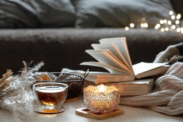 Stillleben mit einer tasse tee, büchern und einer brennenden kerze in einem schönen kerzenhalter. wohnkomfort-konzept.
