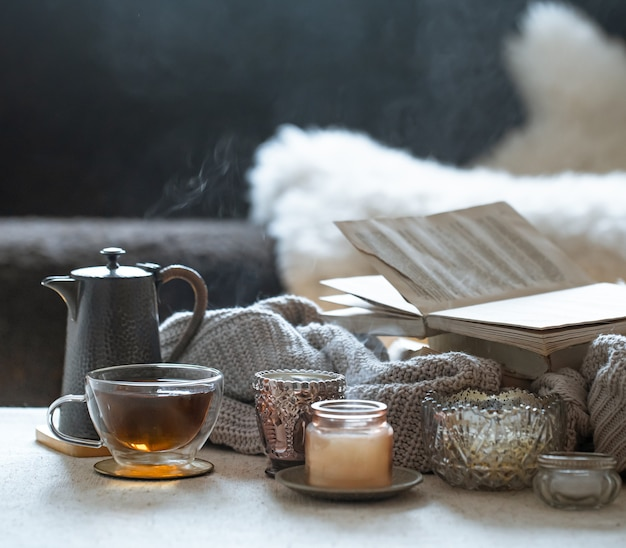 Stillleben mit einer tasse tee, einer teekanne, einem buch und wunderschönen vintage-kerzenleuchtern mit kerzen. wohnkultur-konzept.
