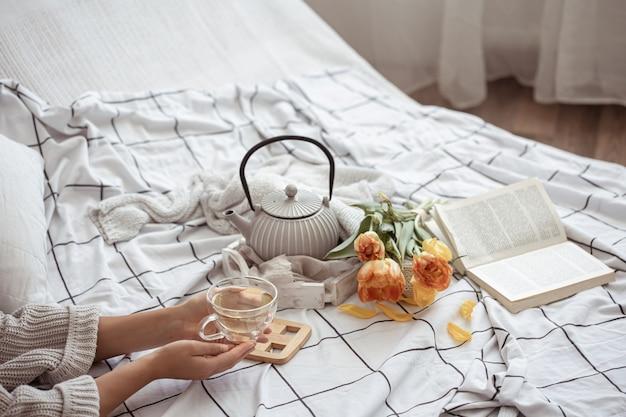Stillleben mit einer tasse tee, einer teekanne, einem strauß tulpen und einem buch im bett