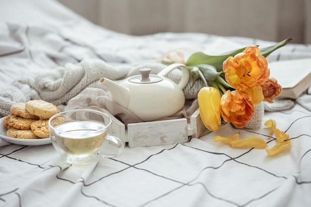 Stillleben mit einer tasse tee, einer teekanne, einem strauß tulpen und keksen im bett. wochenend- und frühlingsmorgenkonzept.