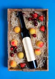 Stillleben mit flasche und früchten auf dem rustikalen hölzernen behälter