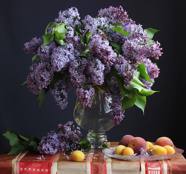 Stillleben mit flieder in einer vase, aprikosen und pfirsichen.