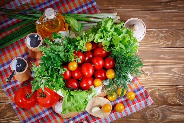 Stillleben mit frischen tomaten, knoblauch und petersilie auf holzbrettern.