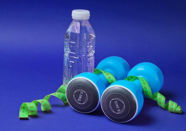 Stillleben mit gesundem lebensstil. kurzhanteln, lineal, flasche wasser auf blau