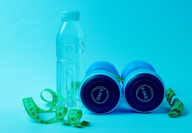 Stillleben mit gesundem lebensstil. kurzhanteln, lineal, flasche wasser auf blauem neon