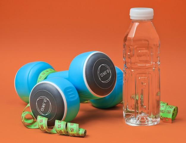Stillleben mit gesundem lebensstil. kurzhanteln, lineal, flasche wasser auf orange