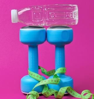 Stillleben mit gesundem lebensstil. kurzhanteln, lineal, flasche wasser auf rosa.