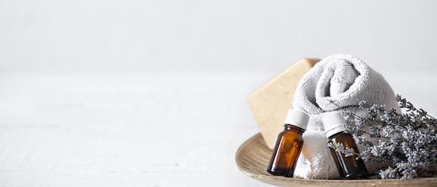 Stillleben mit handtüchern, seife und aromaölen in gläsern. aromatherapie- und gesundheitskonzept.