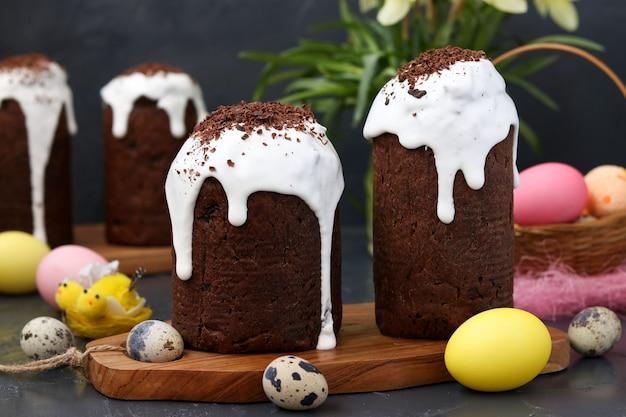 Stillleben mit hausgemachten schokoladen-osterkuchen und bunten eiern auf dunklem hintergrund