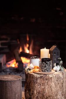 Stillleben mit heißen getränken, kerze und dekor mit brennendem feuer. das konzept eines dorfurlaubs außerhalb der stadt.