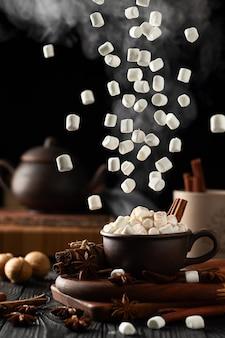 Stillleben mit heißer schokolade und marshmallows. marshmallow fällt von oben. aus dem becher steigt heißer dampf auf