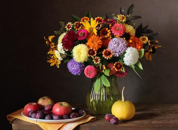 Stillleben mit herbstblumenstrauß von gartenblumen in einer vase, in pflaumen, in äpfeln und in einem kürbis.
