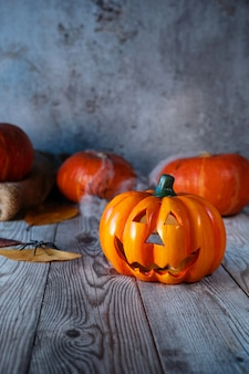 Stillleben mit kürbislaterne, kürbissen, spinnennetz und brennender laterne auf rustikalem tisch. nachtszene. halloween-konzept