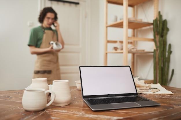 Stillleben mit laptop mit leerem weißem bildschirm auf dem tisch in der werkstatt, mit verschwommenem männlichen handwerker, der im hintergrund telefonisch spricht, konzept für kleinunternehmen und unternehmertum, kopierraum