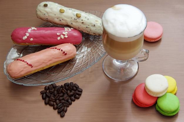 Stillleben mit latte cup, eclairs, makronen und kaffeebohnen