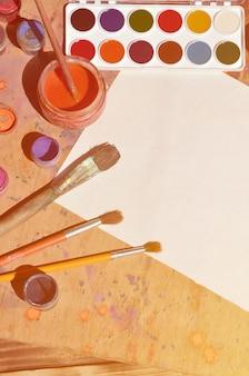 Stillleben mit leerem papier, pinseln und töpfen mit aquarell- und gouachefarbe