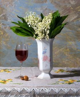 Stillleben mit maiglöckchen in vase, glas wein und bonbons