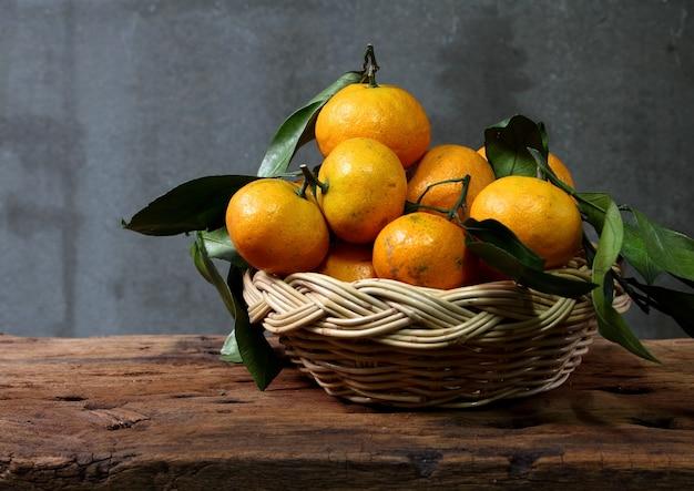 Stillleben mit mandarinen im korb auf holztisch mit grunge-platz