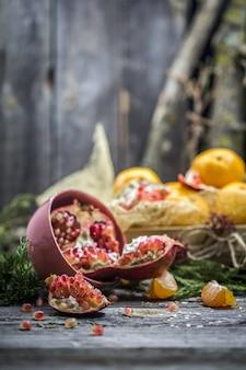 Stillleben mit mandarinen und granatapfel auf holz