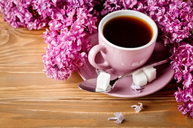 Stillleben mit niederlassungen der flieder und des tasse kaffees auf einem holztisch.