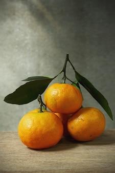 Stillleben mit orangefarbenen früchten auf holztisch mit grunge-platz