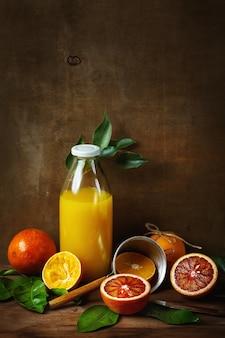 Stillleben mit orangenfrüchten und saft auf holztisch. malstil. selektiver fokus. platz für ihren text.