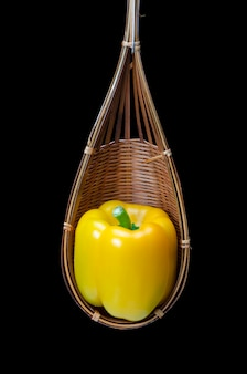 Stillleben mit paprika werden in einen hölzernen korb gelegt, lokalisiert auf schwarzem