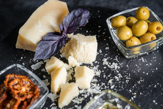 Stillleben mit parmesan, oliven und basilikum.