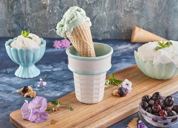 Stillleben mit pistazien und cremigem eis in vasen und kegel auf blauem hintergrund mit blumen.