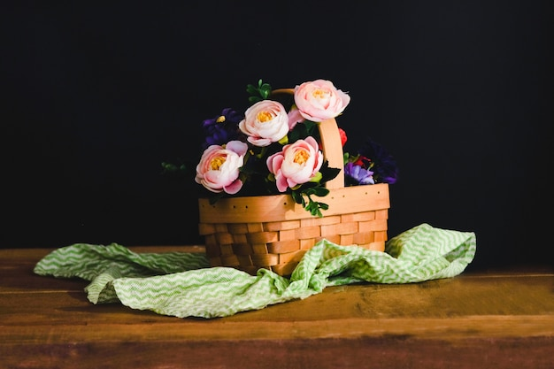 Stillleben mit rosa rosen im korb auf dem tisch.
