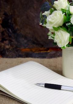 Stillleben mit rosenblüte und notizbuch auf sackleinen