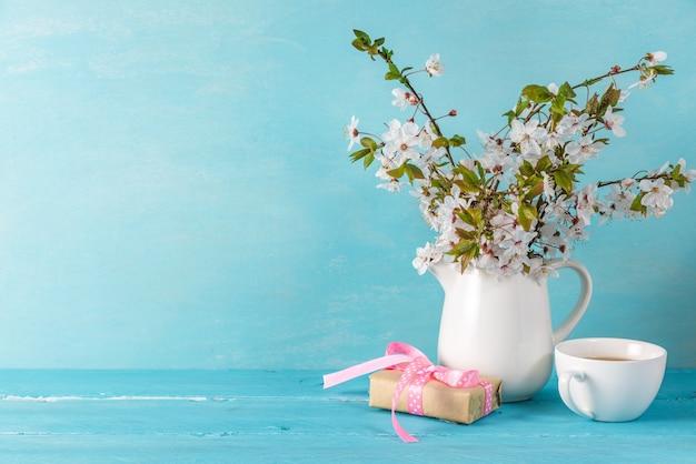 Stillleben mit schönen frühlingskirschblütenblumen, kaffeetasse und geschenkbox auf blauem holztisch mit kopierraum